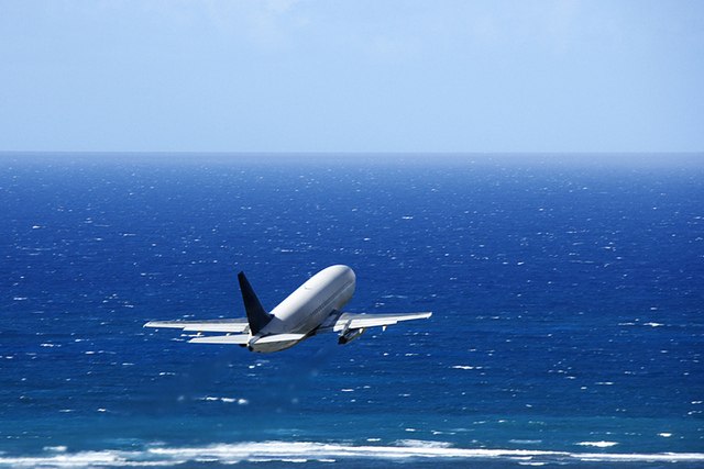 Airplane over ocean.